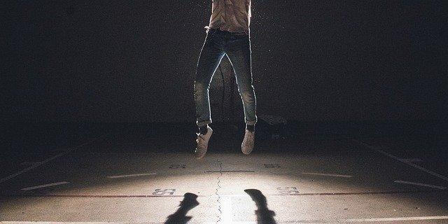 Muž v rifliach a hnedom tričku vyskakuje do výšky v telocvični.jpg