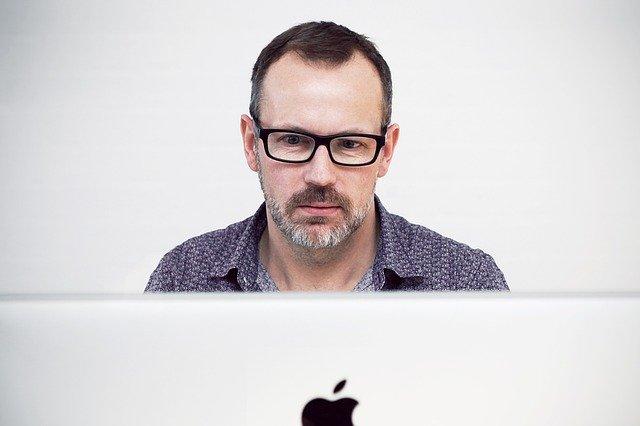 Muž v okuliaroch sedí za počítačom a pozerá na monitor