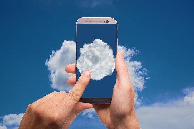 Človek ťuká na smartphone, ktorý má na obrazovke oblohu s mrakmi